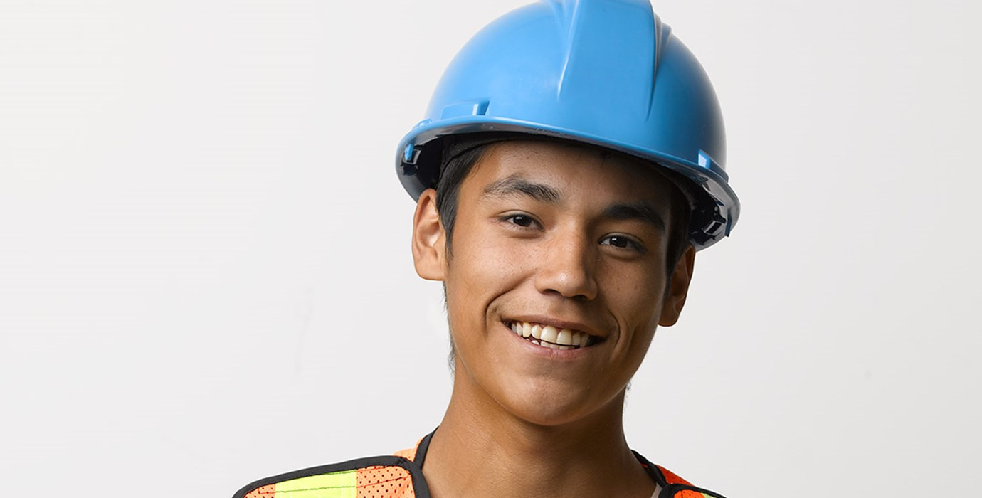 Youth worker wearing a hard hat and safety vest