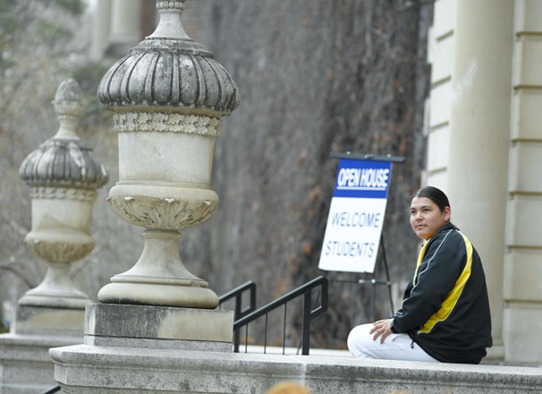 "Student sitting outside a school building with an ""Open House: Welcome Students"" sign in the background"