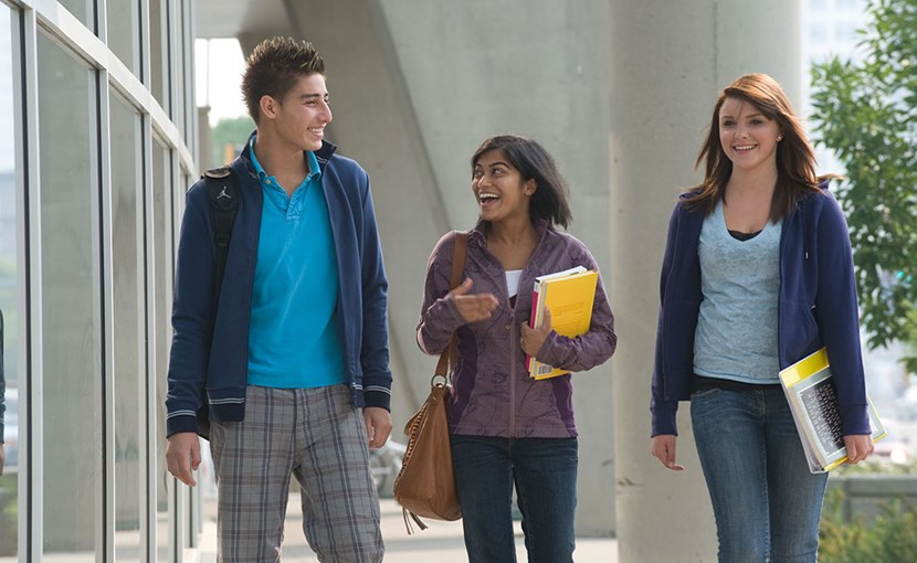 3 students walking outside on campus