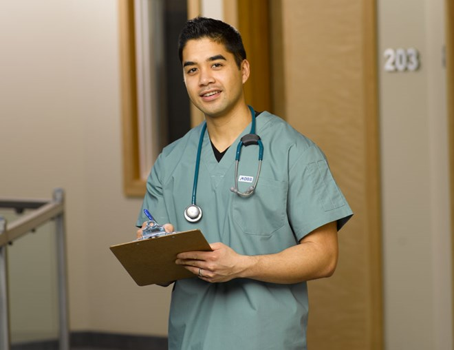 Nurse wearing scrubs with stethoscope around neck, carrying a clipboard stands in a hospital hallway
