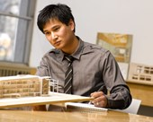 Architect in an office looking at a wooden model of a building