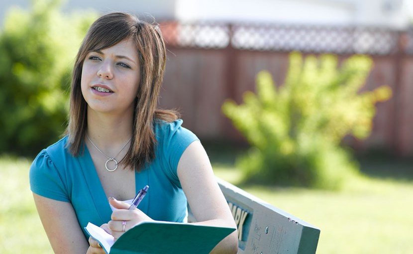 Youth thinking about what to write in a journal while sitting in a park