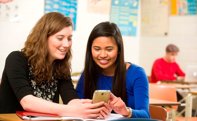 2 high school students looking at a smartphone in a classroom