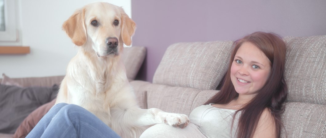 Pregnant youth reclining on sofa with dog