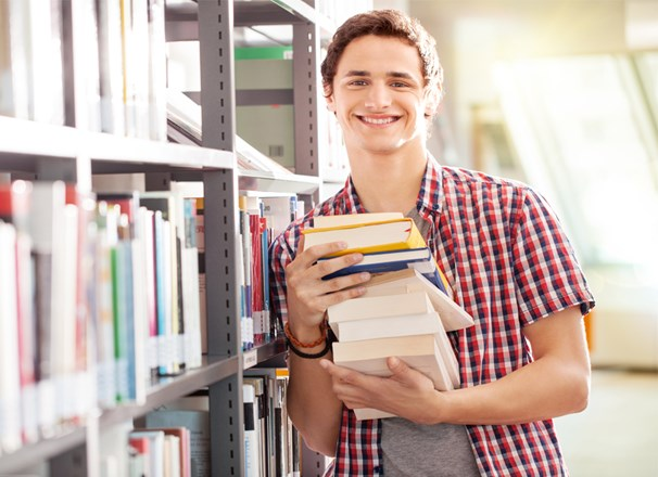 Youth holding a stack of books while leaning against a library shelf
