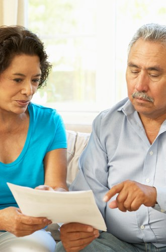 Couple looking at paperwork on the couch
