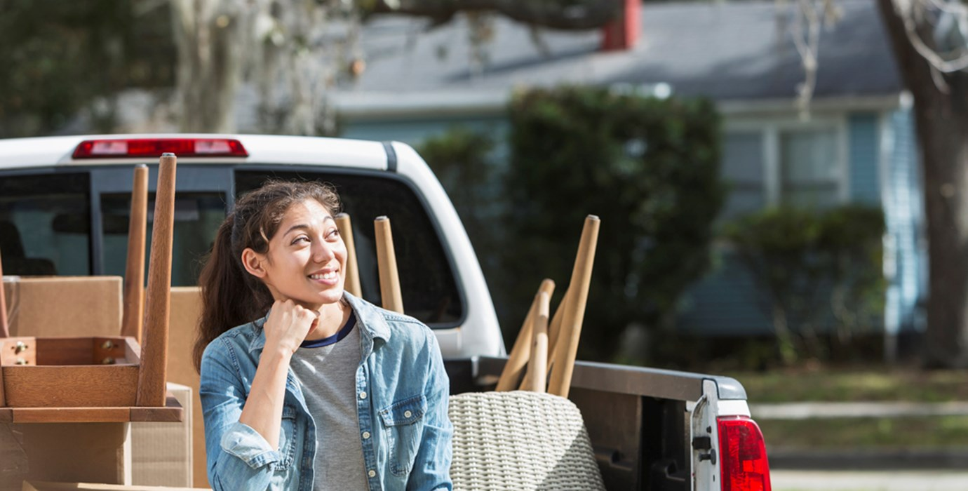 Youth sitting on the bed of a pickup truck full of furniture