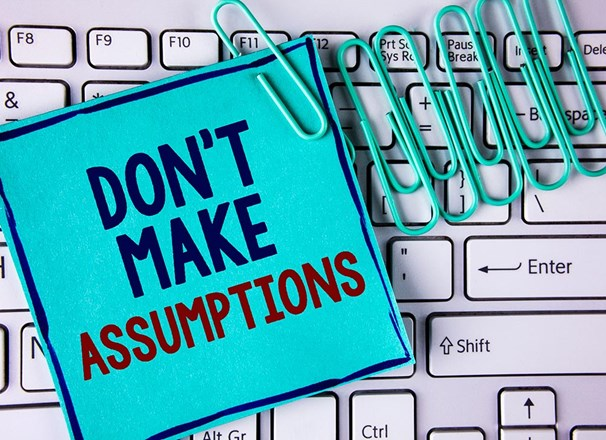 "Note saying ""don't make assumptions"" and paper clips on a keyboard"