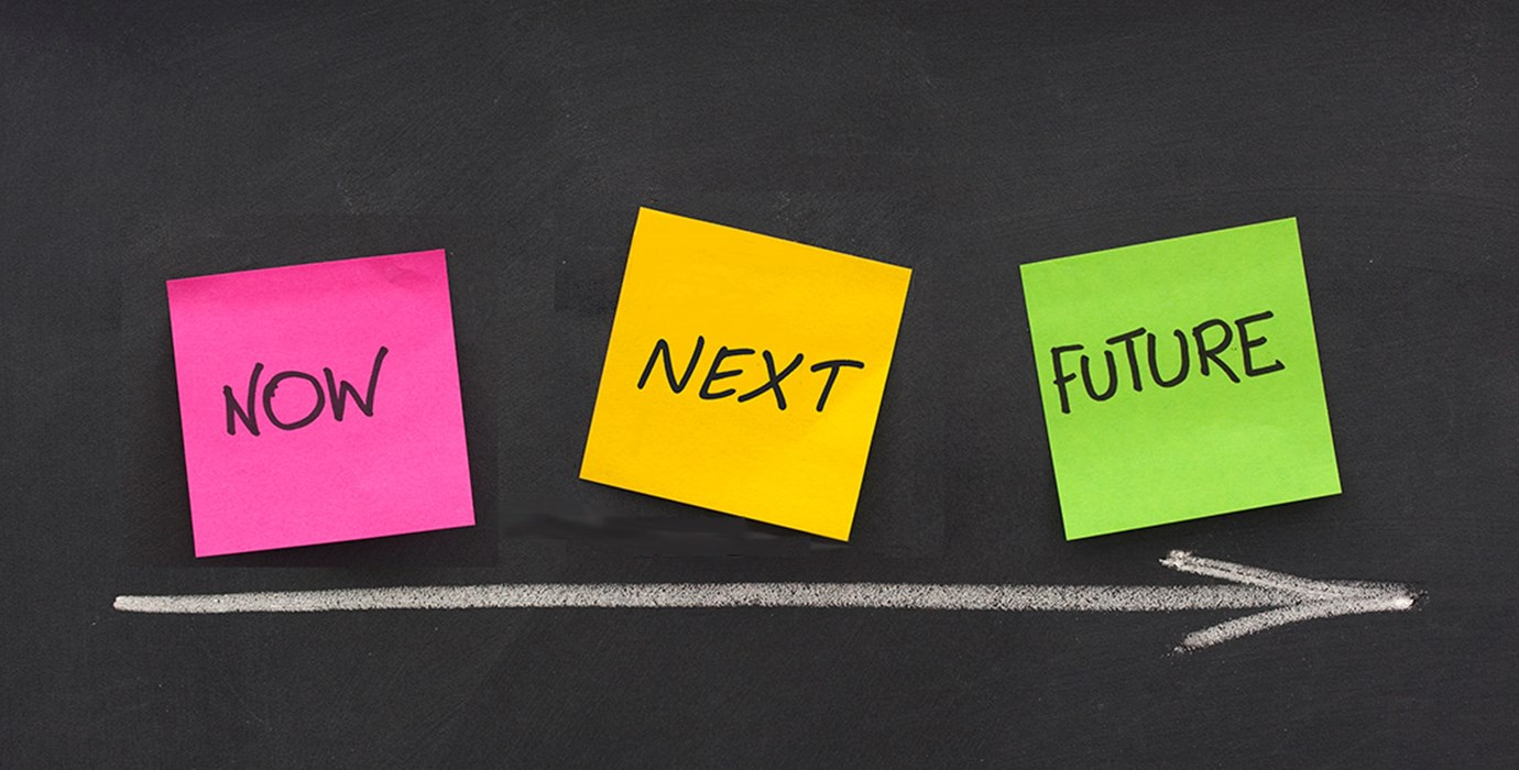 """NOW,"" ""NEXT,"" and ""FUTURE"" written on sticky notes against with an arrow pointing toward ""FUTURE"""