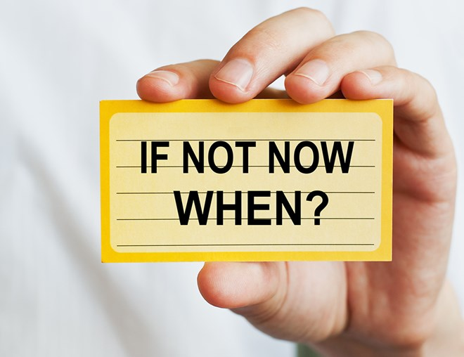 "Hand holding up an index card with the message, ""If not now, when?"""