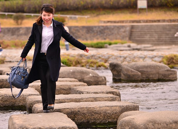 Person wearing office attire carrying a bag stepping on stones across a river