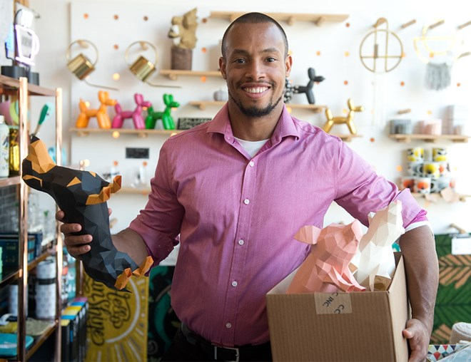 Entrepreneur holding a box of origami in a store