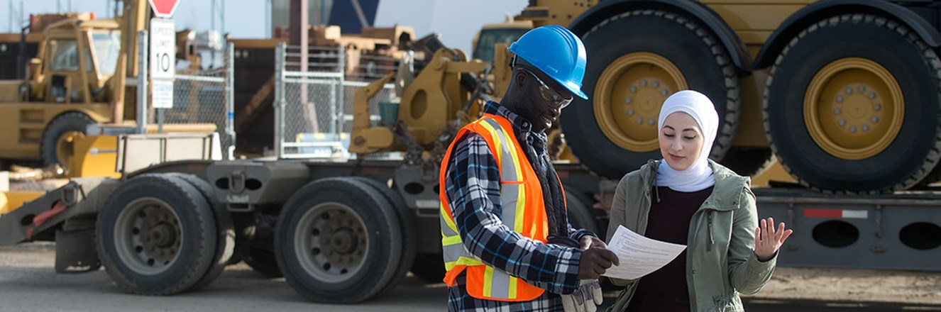 Employees on a jobsite having a discussion in front of large equipment