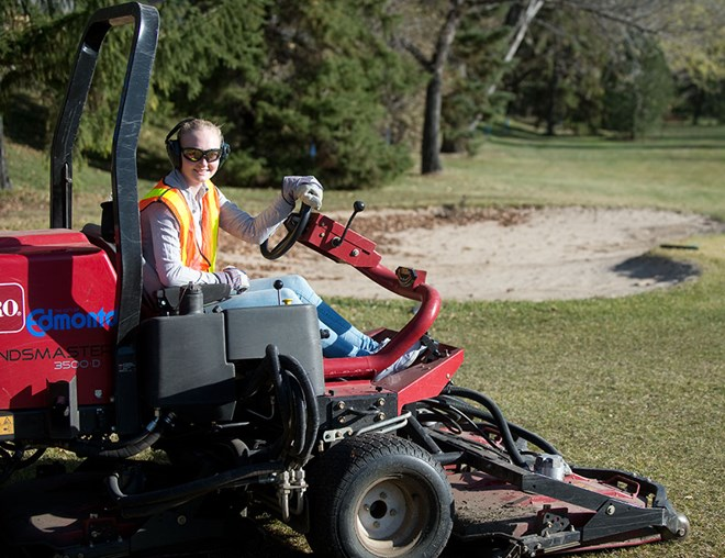 Golf course groundskeeper riding the mower