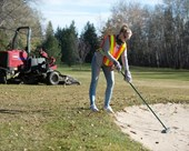 Golf course groundskeeper working on a sand bunker