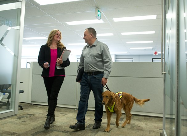 Employee with service dog talking with another employee in the office