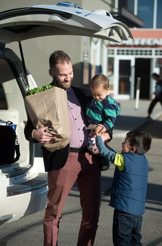 Parent and children putting groceries in the trunk of a car