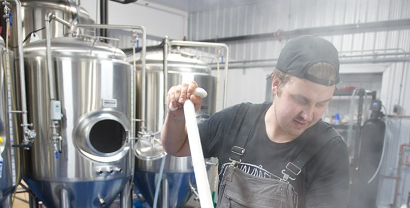 Entrepreneur in a brewery mixing ingredients in brewing tank