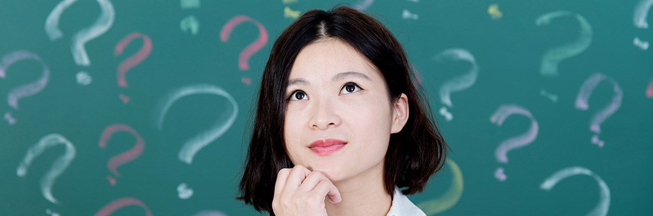 Person looking up with chin in hand in front of a background of question marks