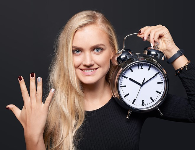 Person holding up 5 fingers and holding an alarm clock