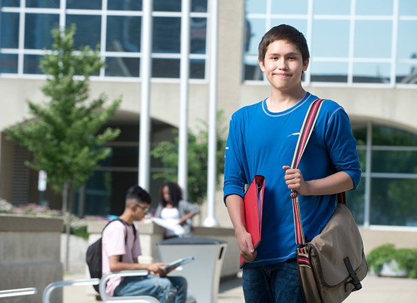 Youth student standing outside campus building