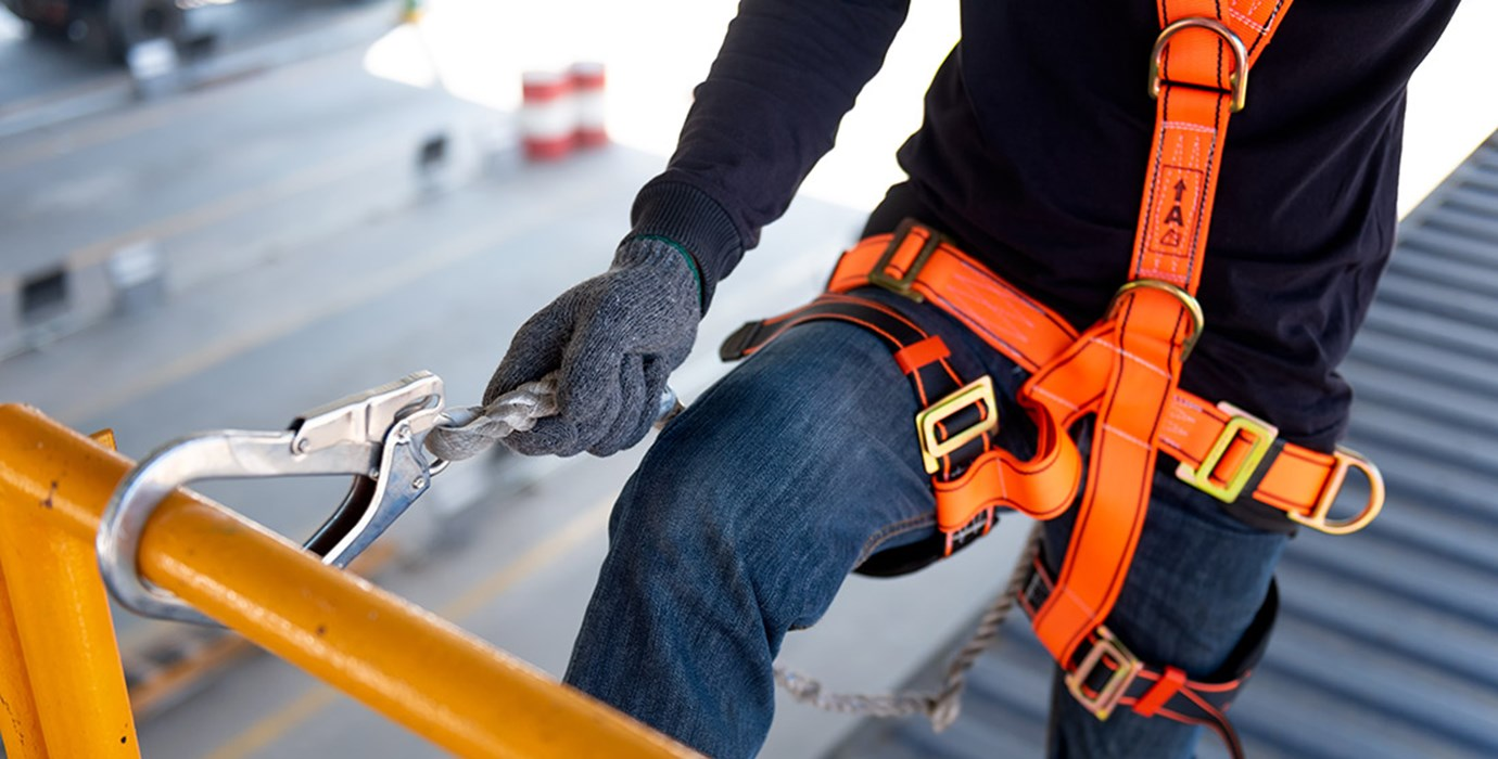 Construction worker wearing an orange harness with safety hook on railing