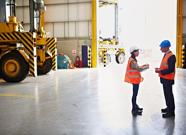 Employee and manager wearing hard hats discussing in a warehouse