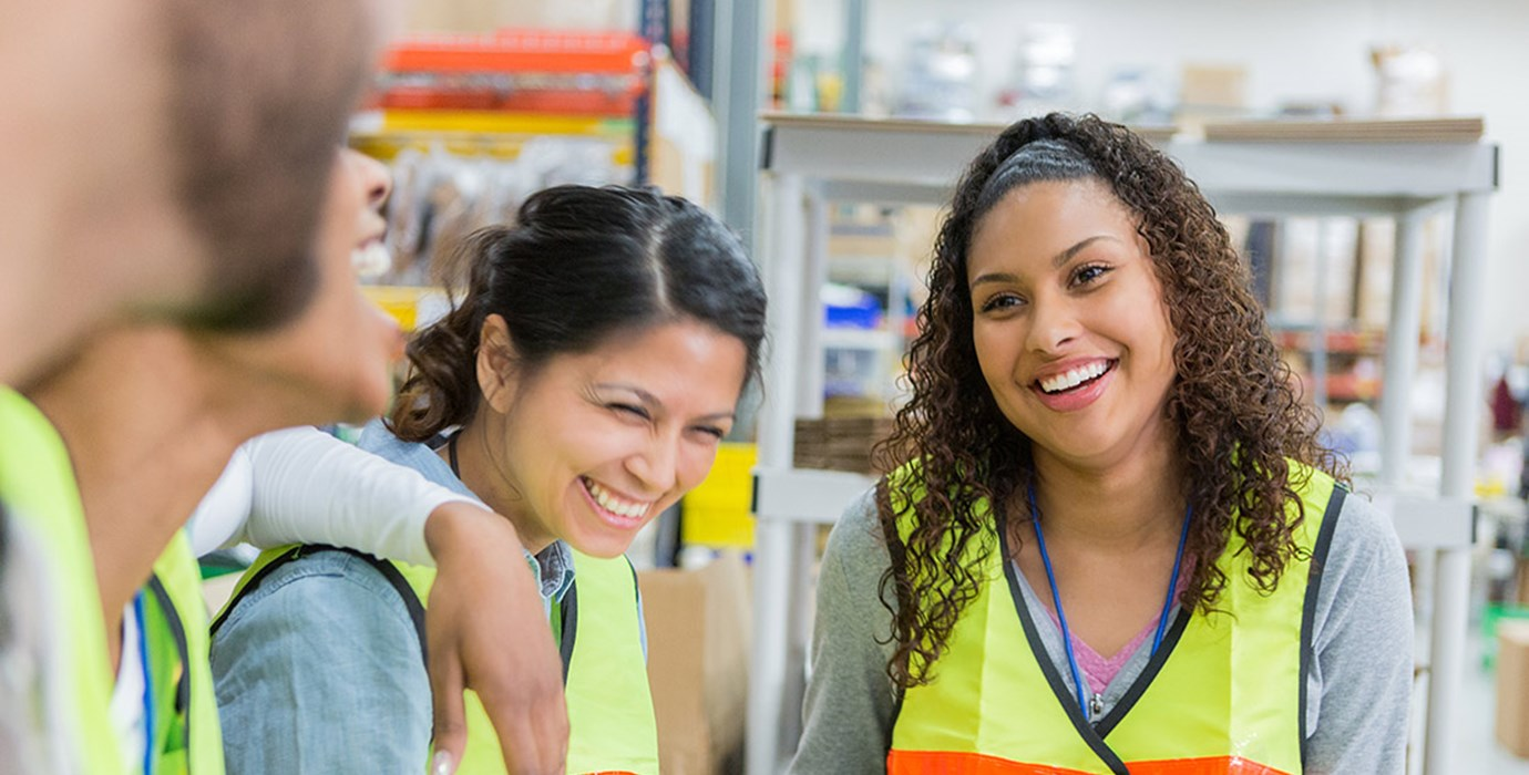 Employees wearing safety vests smiling in a warehouse