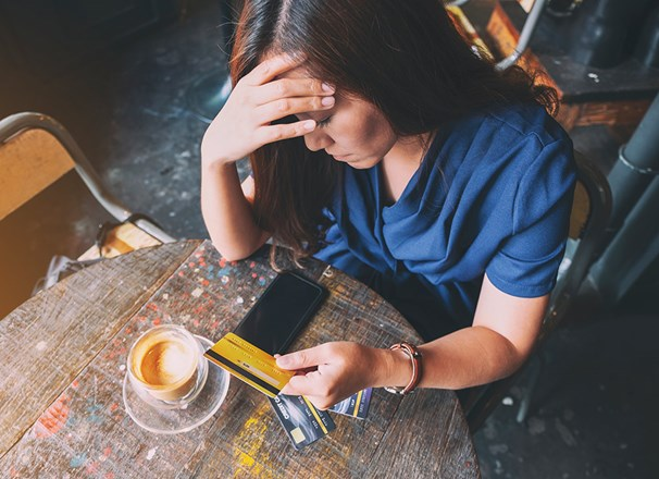 Person having a coffee with head in hand unhappily holding a credit card