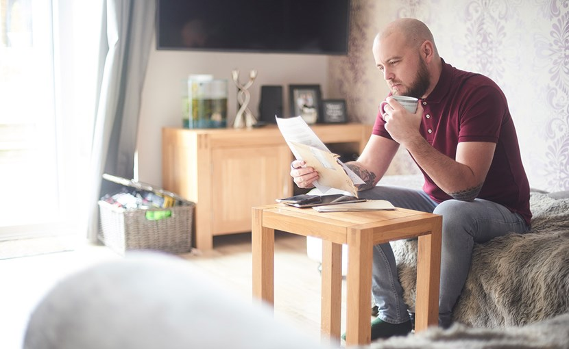 Person reviewing paperwork while sitting in the living room