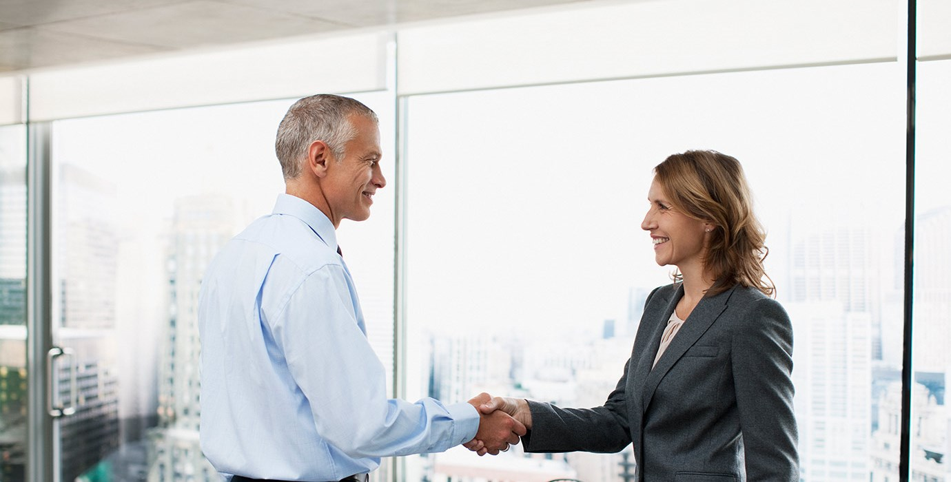 2 people in a boardroom shaking hands and smiling
