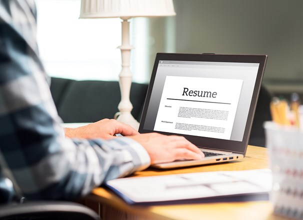 Hands typing on a laptop with the screen showing a resume