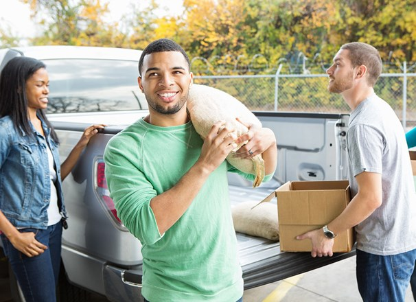 Volunteer carrying a sack of food out of a pickup truck