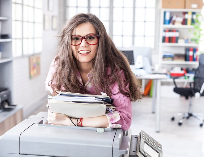 Person wearing glasses, carrying documents, and leaning on a copier in an office