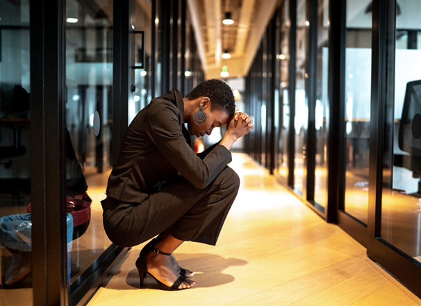 Worried person with head in hands crouched in an office hallway