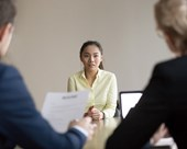 Job seeker facing 2 interviewers in a meeting room