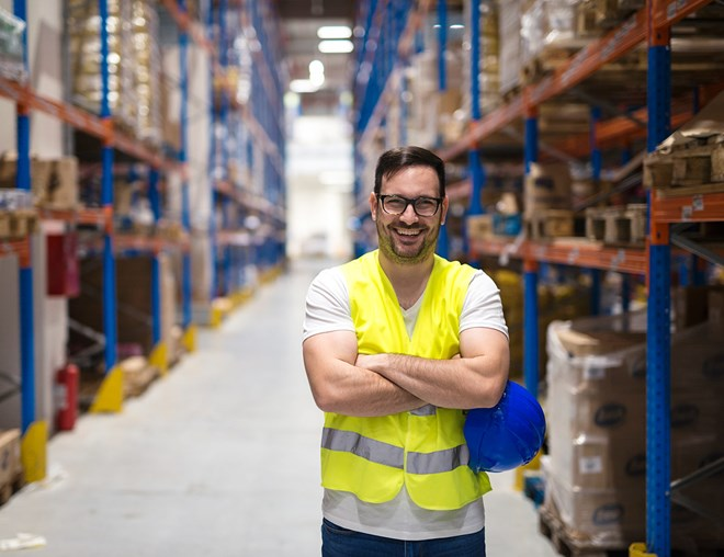 Worker wearing a safety vest smiling and standing in an aisle of a distribution centre