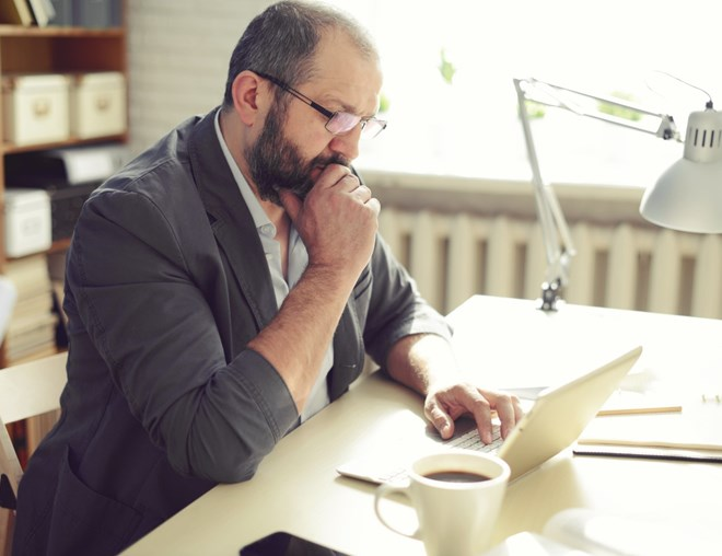 Man thinking while using laptop at his desk