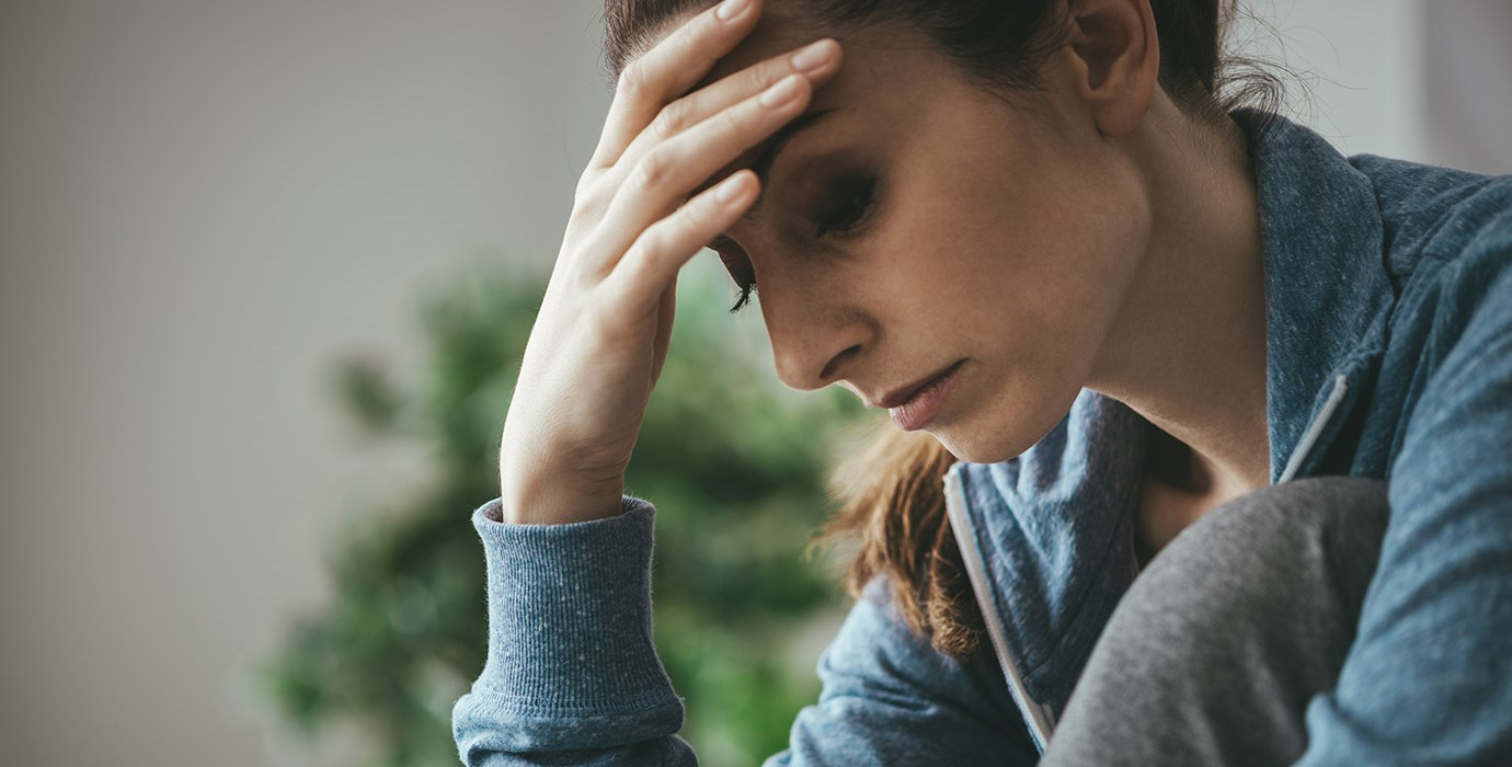 Depressed woman holder her forehead and looking downward.