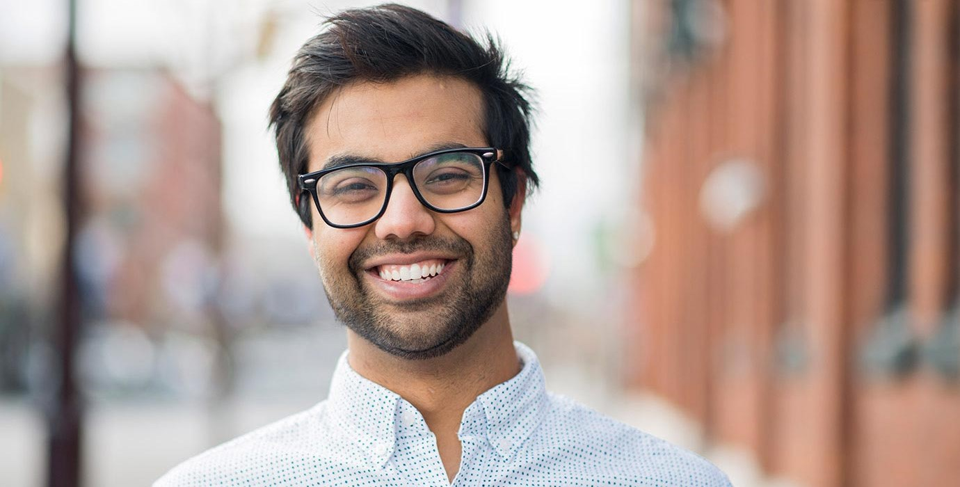 Smiling young man in collared shirt and glasses.