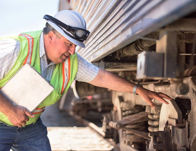 Railroad worker inspecting a train.