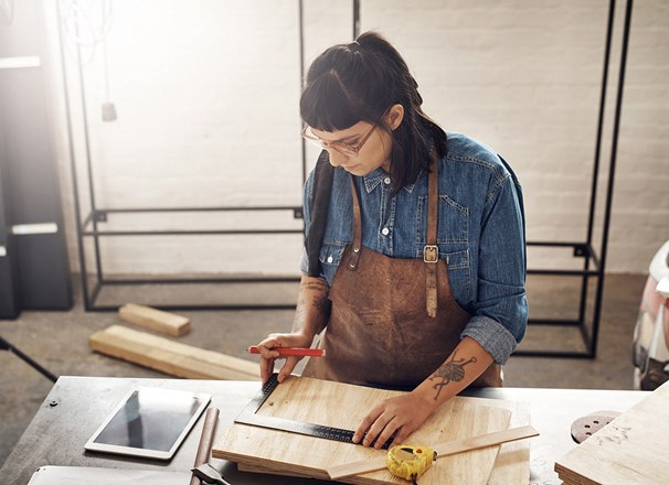 Woman doing woodworking while looking at a tablet in her workshop.