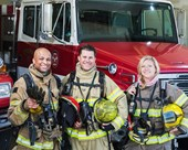 Diverse group of firefighters standing beside a firetruck.